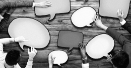 black and white photo, people sitting around table holding speech bubbles