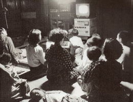 Black and white photo of family sitting around old TV