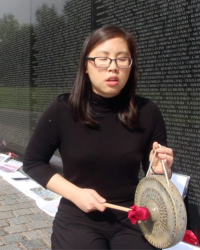 Photo of woman playing a gong in front of Vietnam Veterans memorial with eyes closed