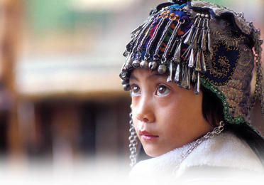 Child looking up, wearing traditional Chinese beaded hat