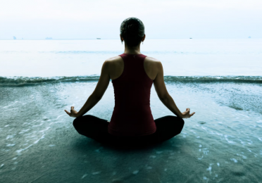 Silhouette of person sitting cross-legged and meditating