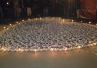 Paper cranes laid out in the shape of a heart with candles surrounding